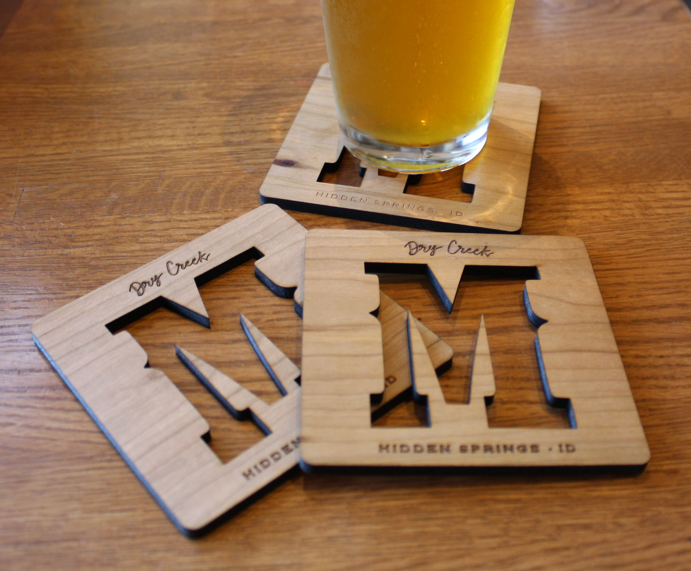 Wood coasters in American Cherry with cutout logo and laser engraving